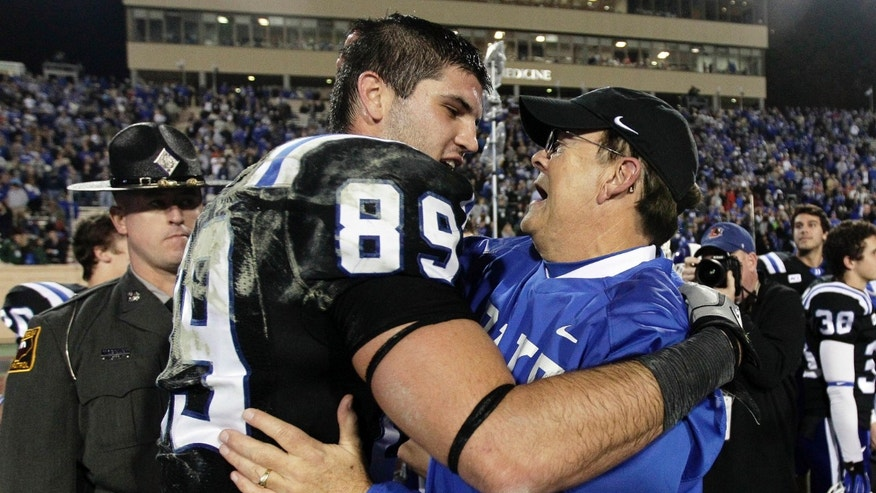 Duke coach David Cutcliffe hugs Braxton Deaver (89) following an NCAA college football game against Miami in Durham, N.C., Saturday, Nov. 16, 2013. Duke won 48-30. (AP Photo/Gerry Broome)