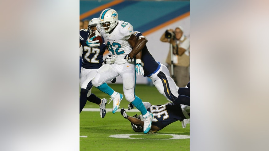 Miami Dolphins tight end Charles Clay (42) breaks up tackles by San Diego Chargers strong safety Marcus Gilchrist (38) and linebacker Donald Butler (56) for a 39-yard run for a touchdown during the second half of an NFL football game, Sunday, Nov. 17, 2013, in Miami Gardens, Fla. (AP Photo/Wilfredo Lee)