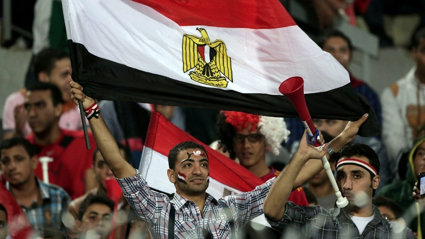 An Egyptian supporter waves a national flag during the World Cup qualifying playoff second leg soccer match, at the Air Defense Stadium in Cairo, Egypt, Tuesday, Nov. 19, 2013. (AP Photo/Manu Brabo)