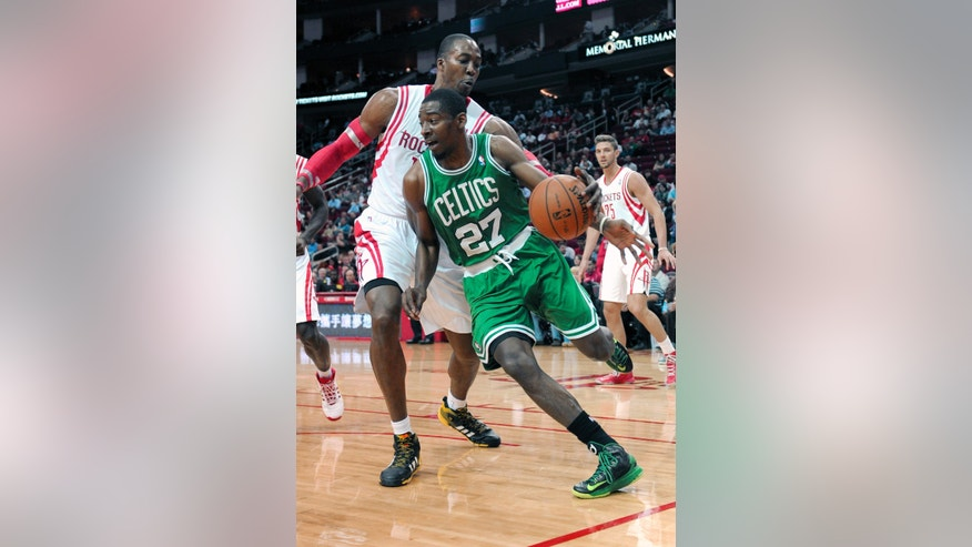 Boston Celtics' Jordan Crawford (27) drives the ball around Houston Rockets' Dwight Howard, left, in the first half of an NBA basketball game Tuesday, Nov. 19, 2013, in Houston. (AP Photo/Pat Sullivan)