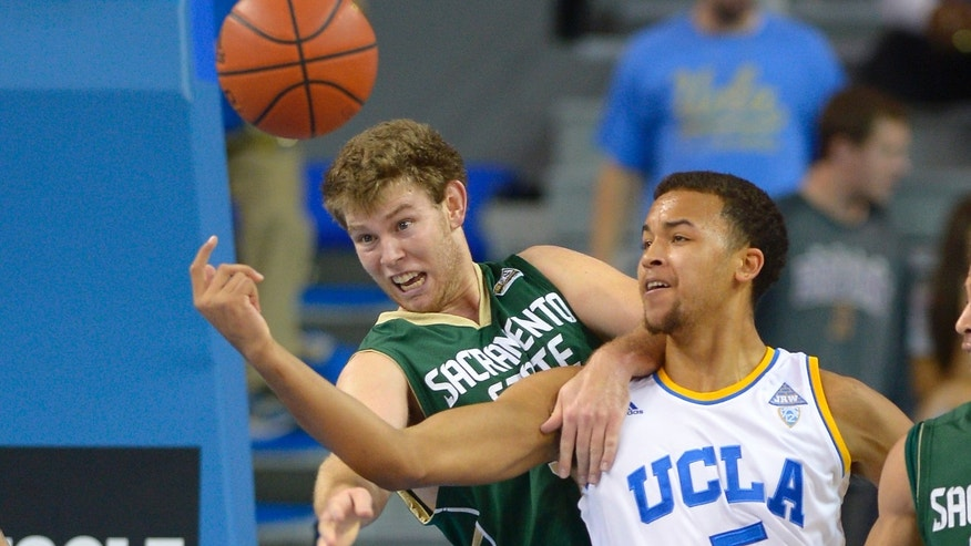 Sacramento forward Alex Tiffin, left, and UCLA forward Kyle Anderson battle for a loose ball during the first half of an NCAA college basketball game, Monday, Nov. 18, 2013, in Los Angeles.  (AP Photo/Mark J. Terrill)