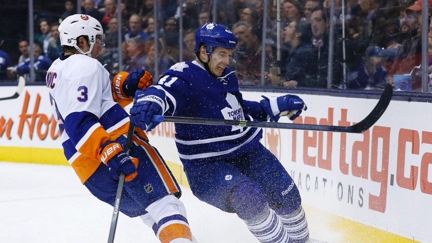 Toronto Maple Leafs' Nikolai Kulemin, right, battles for the puck with New York Islanders' Travis Hamonic during the second period of an NHL hockey game, Tuesday, Nov. 19, 2013 in Toronto. (AP Photo/The Canadian Press, Mark Blinch)