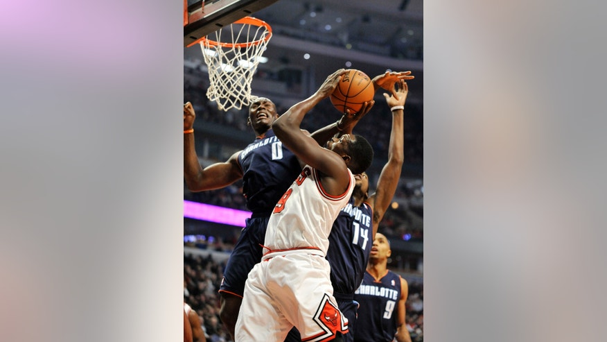 Chicago Bulls' Luol Deng (9), of South Sudan goes up for a shot against Charlotte Bobcats' Bismack Biyombo (0), of Congo, and Michael Kidd-Gilchrist (14), during the first quarter of an MLB basketball game in Chicago, Monday, Nov. 18, 2013. (AP Photo/Paul Beaty)