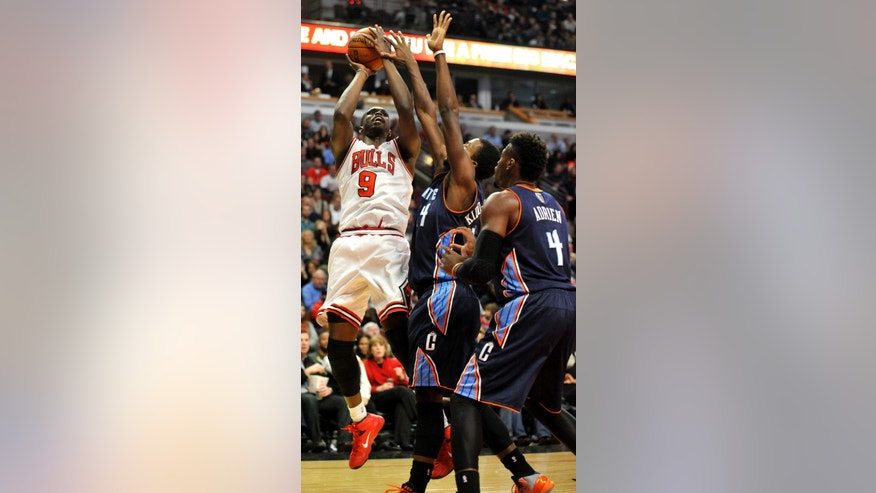 Chicago Bulls' Luol Deng (9), of South Sudan, goes up for a shot against against Charlotte Bobcats' Michael Kidd-Gilchrist (14), and Jeff Adrien (4), during the second quarter of an NBA basketball game in Chicago, Monday, Nov. 18, 2013. (AP Photo/Paul Beaty)