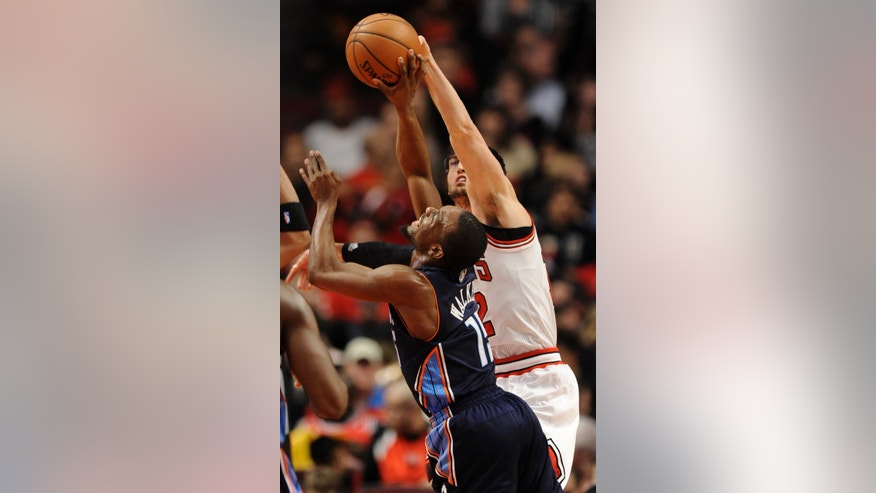 Charlotte Bobcats' Kemba Walker (15), goes up for a shot against Chicago Bulls' Kirk Hinrich (12), during the first quarter of an NBA basketball game in Chicago, Monday, Nov. 18, 2013. (AP Photo/Paul Beaty)