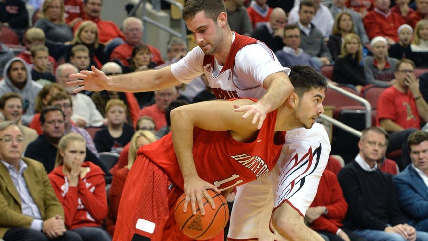 Hartford's Taylor Dyson, front, attempts to duck under the defensive pressure of Louisville's Luke Hancock during first half action of their NCAA mens college basketball game Nov. 19, 2013, in Louisville, Ky. (AP Photo/Timothy D. Easley)
