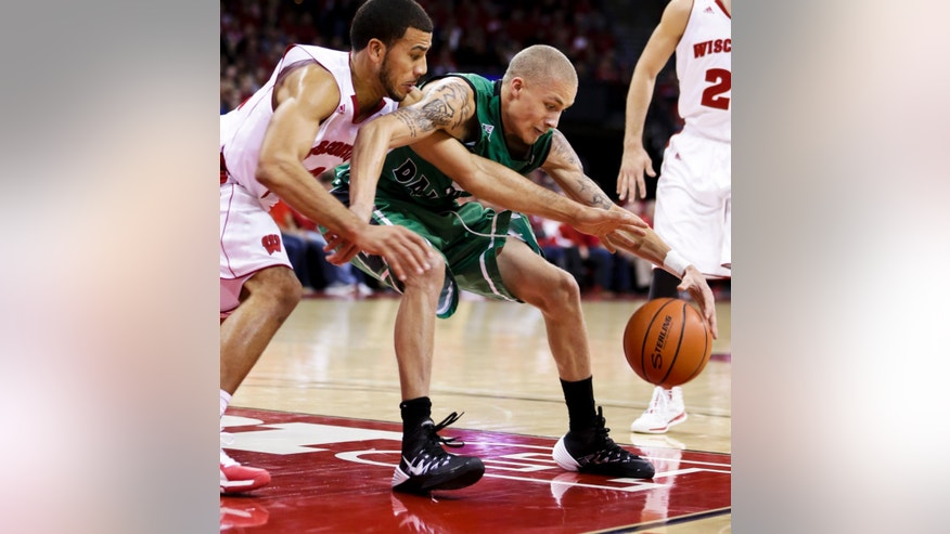 Wisconsin's Traevon Jackson, left, reaches in on North Dakota's Troy Huff during the first half of an NCAA college basketball game Tuesday, Nov. 19, 2013, in Madison, Wis. (AP Photo/Andy Manis)