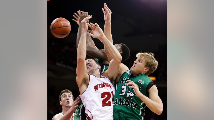 North Dakota's Jaron Nash, top, and Josh Schuler (32) battle with Wisconsin's Josh Gasser (21) for a rebound during the first half of an NCAA college basketball game Tuesday, Nov. 19, 2013, in Madison, Wis. At left is Wisconsin's Frank Kaminsky. (AP Photo/Andy Manis)