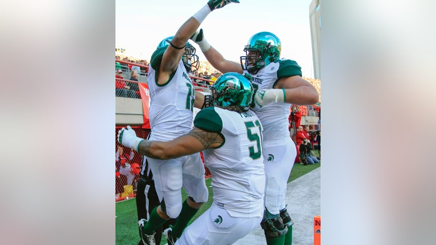 Michigan State tackle Dan France, right, and tackle Fou Fonoti (51) celebrate with R.J. Shelton, left, after Shelton scored a touchdown against Nebraska in the first half of an NCAA college football game in Lincoln, Neb., Saturday, Nov. 16, 2013. (AP Photo/Nati Harnik)