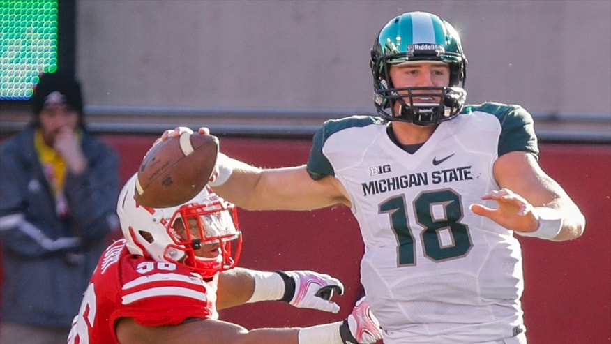 Michigan State quarterback Connor Cook (18) throws under pressure from Nebraska defensive tackle Aaron Curry (96) in the first half of an NCAA college football game in Lincoln, Neb., Saturday, Nov. 16, 2013. (AP Photo/Nati Harnik)