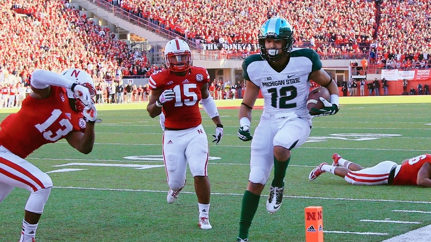 Michigan State's R.J. Shelton (12) scores a touchdown against Nebraska linebacker Zaire Anderson (13) and linebacker Michael Rose (15) in the first half of an NCAA college football game in Lincoln, Neb., Saturday, Nov. 16, 2013. (AP Photo/Nati Harnik)
