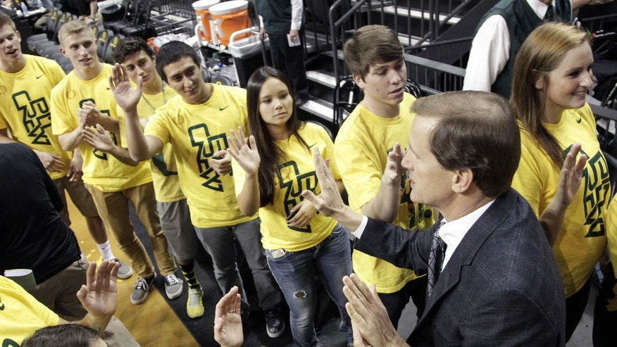Oregon basketball coach Dana Altman is greeted by members of the 'Pit Crew' as he walks on to the court before an NCAA college basketball game against Utah Valley in Eugene, Ore., Tuesday, Nov. 19, 2013. (AP Photo/Don Ryan)