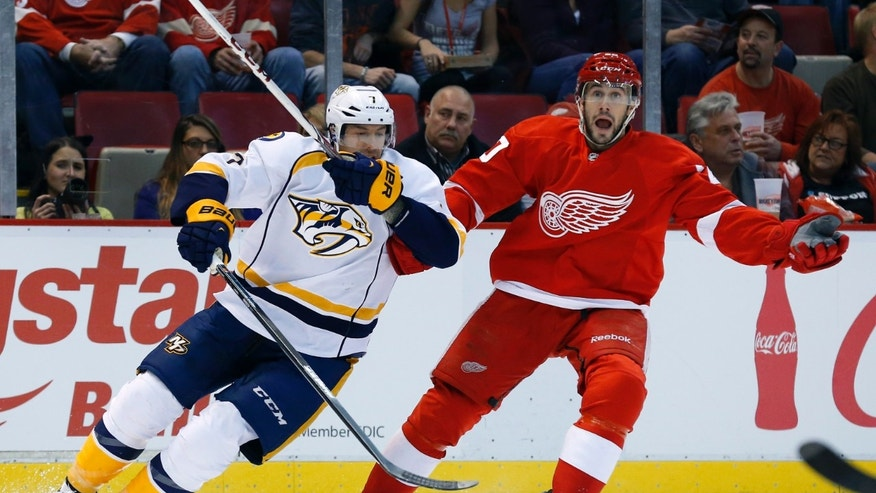 Detroit Red Wings left wing Drew Miller, right, reacts to being held by Nashville Predators center Matt Cullen in the first period of an NHL hockey game in Detroit, Tuesday, Nov. 19, 2013. (AP Photo/Paul Sancya)