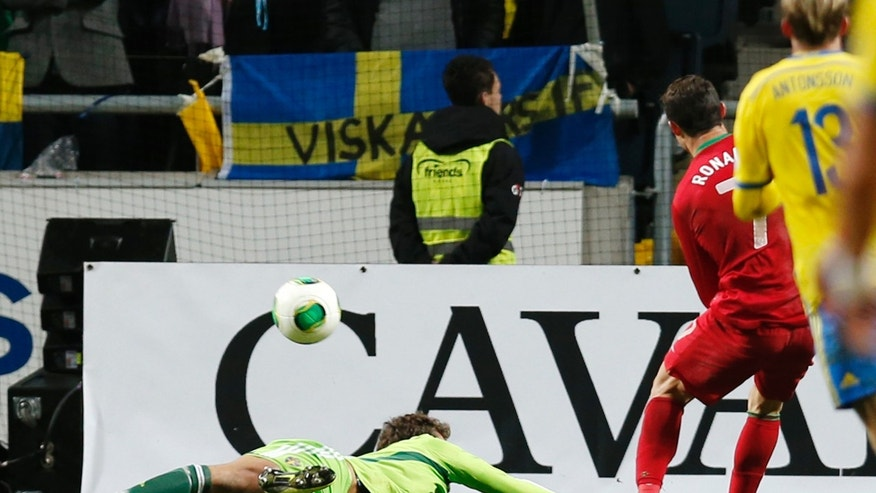 Portugal's Cristiano Ronaldo scores his side's 3rd goal past Sweden goalkeeper Andreas Isaksson, left, during the World Cup qualifying playoff second leg soccer match between Sweden and Portugal in Stockholm, Sweden, Tuesday, Nov.19, 2013. (AP Photo/Frank Augstein)