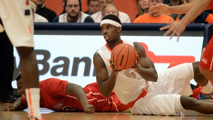 Syracuse's C. J. Fair looks for someone to pass to after grabbing a loose ball against St. Francis during the first half of an NCAA college basketball game in Syracuse, N.Y., Monday, Nov. 18, 2013. (AP Photo/Kevin Rivoli)
