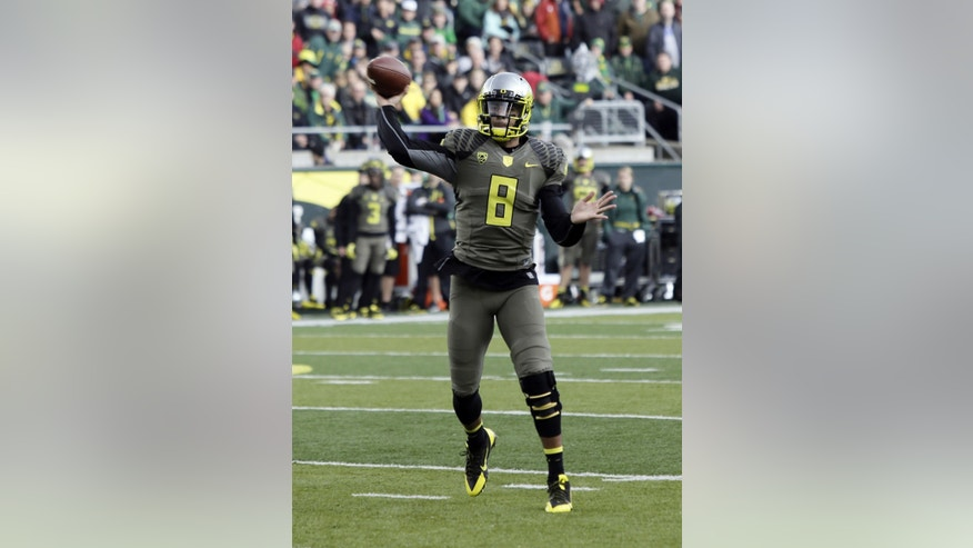 Oregon quarterback Marcus Mariota throws for a touchdown during the first half of an NCAA college football game against Utah  in Eugene, Ore., Saturday, Nov. 16, 2013. (AP Photo/Don Ryan)