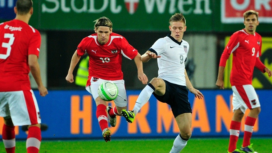 Austria's Christoph Leitgeb, left, and Aron Johannsson of US challenge for the ball during a friendly soccer match between Austria and The United States in Vienna, Austria, Tuesday, Nov. 19, 2013. (AP Photo/Hans Punz)