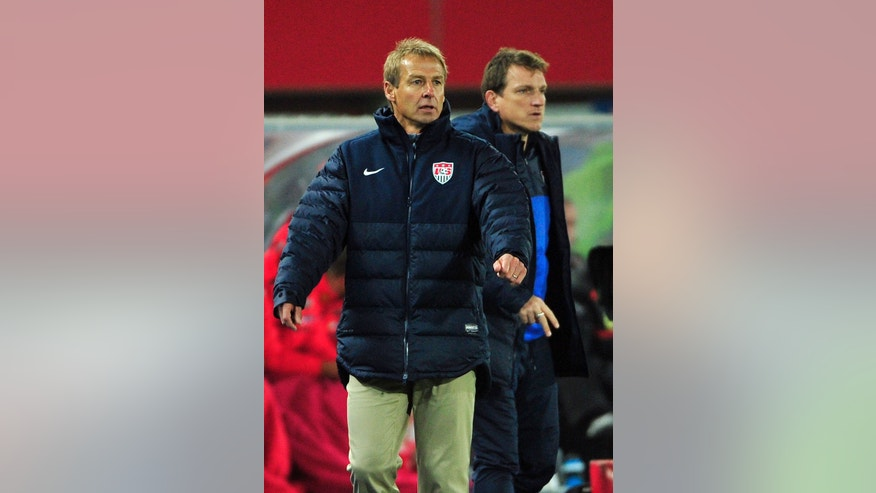 US national soccer team coach Juergen Klinsmann, left, and assistant coach Andreas Herzog react during a friendly soccer match between Austria and The United States in Vienna, Austria, Tuesday, Nov. 19, 2013. (AP Photo/Hans Punz)