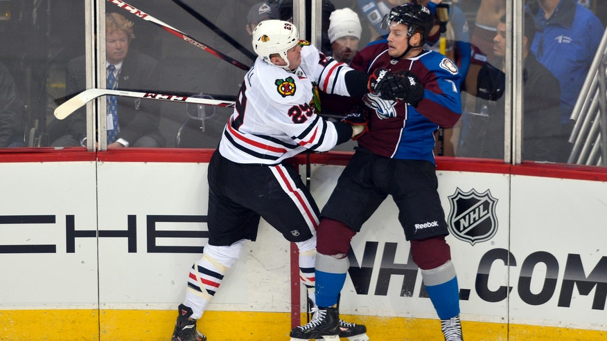 Colorado Avalanche center John Mitchell (7) is checked into the boards by Chicago Blackhawks left wing Bryan Bickell (29) during the first period of an NHL hockey game Tuesday, Nov. 19, 2013, in Denver. (AP Photo/Jack Dempsey)