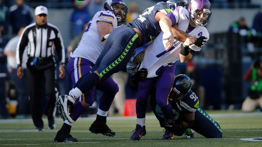 Minnesota Vikings quarterback Christian Ponder, right, is hit by Seattle Seahawks' Michael Bennett, second from left, and Brandon Mebane (92), right, as he attempts a pass in the first half of an NFL football game Sunday, Nov. 17, 2013, in Seattle. The Seahawks won 41-20. (AP Photo/John Froschauer)