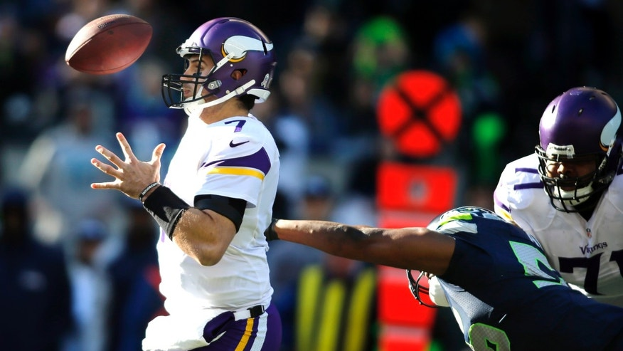 Minnesota Vikings quarterback Christian Ponder, left, loses the ball as he is hit by Seattle Seahawks' Cliff Avril in the first half of an NFL football game Sunday, Nov. 17, 2013, in Seattle. (AP Photo/John Froschauer)