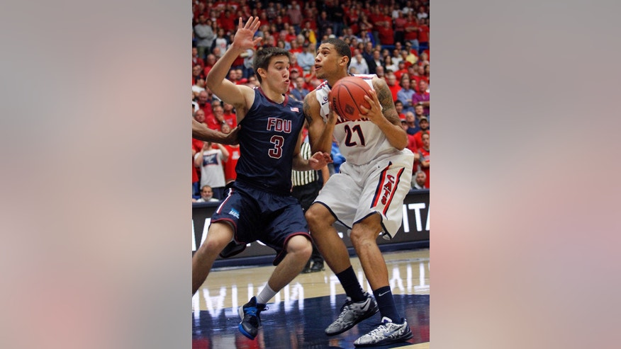 Arizona's Brandon Ashley (21) struggles with Fairleigh Dickinson's Matt MacDonald (3) in the first half of an college NCAA basketball game, Monday, Nov. 18, 2013 in Tucson, Ariz. This is in the first round of the  Preseason NIT. (AP Photo/John Miller)