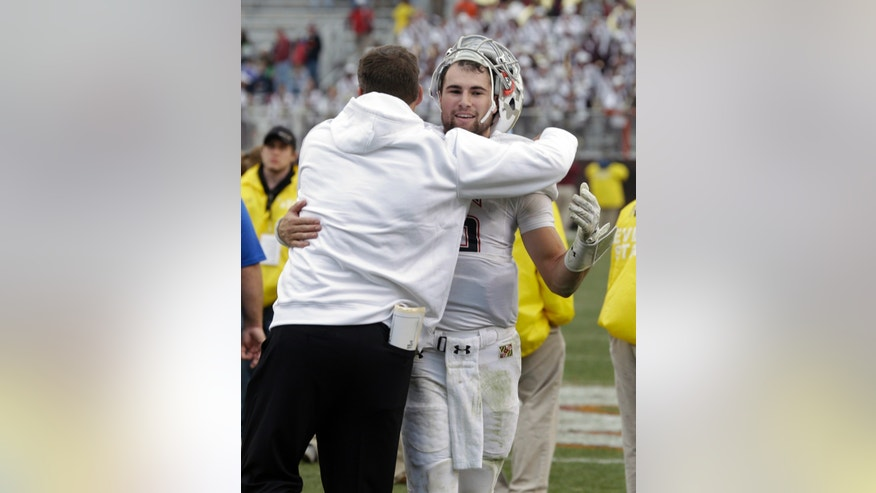 Maryland quarterback C.J. Brown, right, gets a hug from head coach Randy Edsall after their 27-24 win over Virginia Tech  in an NCAA college football game in Blacksburg, Va., Saturday, Nov. 16, 2013. (AP Photo/Steve Helber)