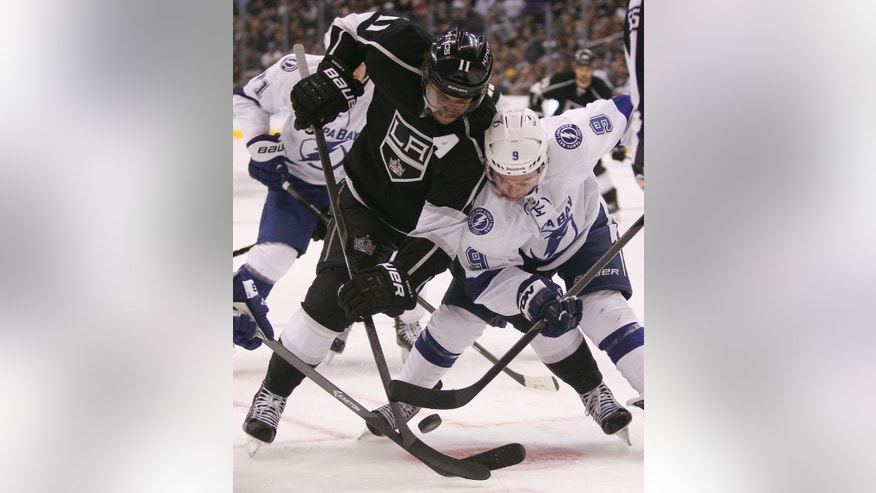 Los Angeles Kings center Anze Kopitar (11), of Yugoslavia battles Tampa Bay Lightning center Tyler Johnson (9) for the puck in the second period of an NHL hockey game Tuesday, Nov. 19, 2013, in Los Angeles.  (AP Photo/Alex Gallardo)