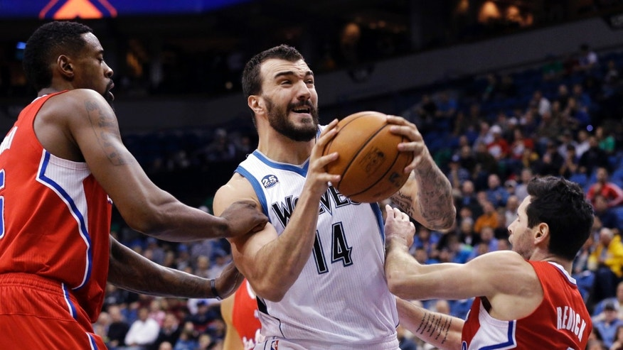 Minnesota Timberwolves' Nikola Pekovic, center, of Montenegro, prepares to shoot as he is double-teamed by Los Angeles Clippers' DeAndre Jordan, left, and J.J. Redick in the first quarter of an NBA basketball game, Wednesday, Nov. 20, 2013, in Minneapolis. (AP Photo/Jim Mone)