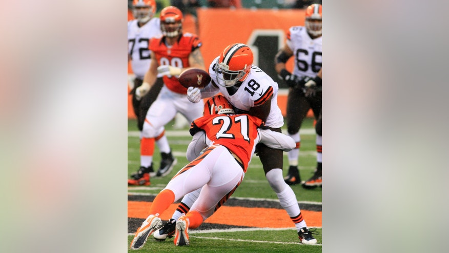 Cleveland Browns wide receiver Greg Little (18) fumbles the ball as he is hit by Cincinnati Bengals defensive back Brandon Ghee (21) in the second half of an NFL football game, Sunday, Nov. 17, 2013, in Cincinnati. (AP Photo/Tom Uhlman)