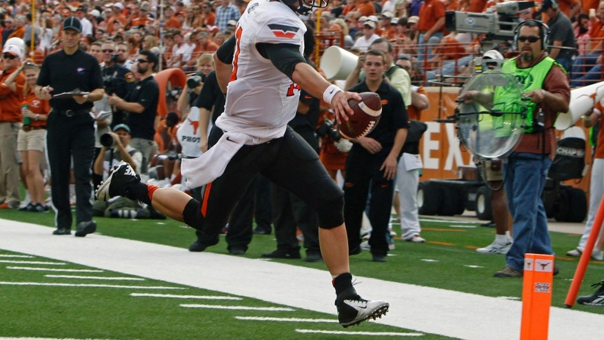 Oklahoma State quarterback Clint Chelf scores a touchdown against Texas during the second quarter of an NCAA college football game Saturday, Nov. 16, 2013, in Austin, Texas. (AP Photo/Michael Thomas)