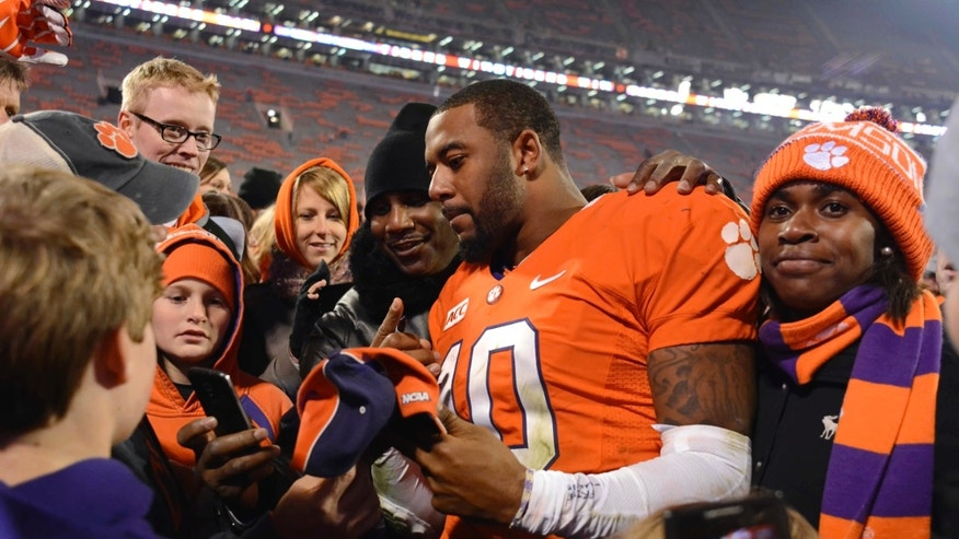 Clemson quarterback Tajh Boyd signs autographs for fans after Clemson defeated Georgia Tech 55-31 in an NCAA college football game Thursday, Nov. 14, 2013, at Memorial Stadium in Clemson, S.C. (AP Photo/ Richard Shiro)