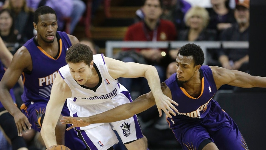 Phoenix Suns guard Ish Smith, right, tries to steal the ball from Sacramento Kings guard Jimmer Fredette during the first quarter of an NBA basketball game in Sacramento, Calif., Tuesday, Nov. 19, 2013.(AP Photo/Rich Pedroncelli)
