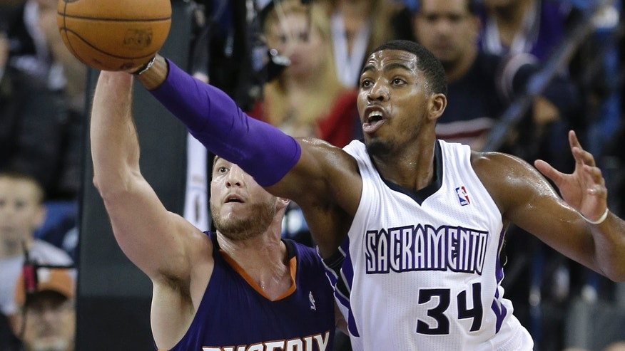 Phoenix Suns center Miles Plumlee, left,  tries to steal the pass intended for Sacramento Kings forward Jason Thompson during the first quarter of an NBA basketball game in Sacramento, Calif., Tuesday, Nov. 19, 2013.(AP Photo/Rich Pedroncelli)