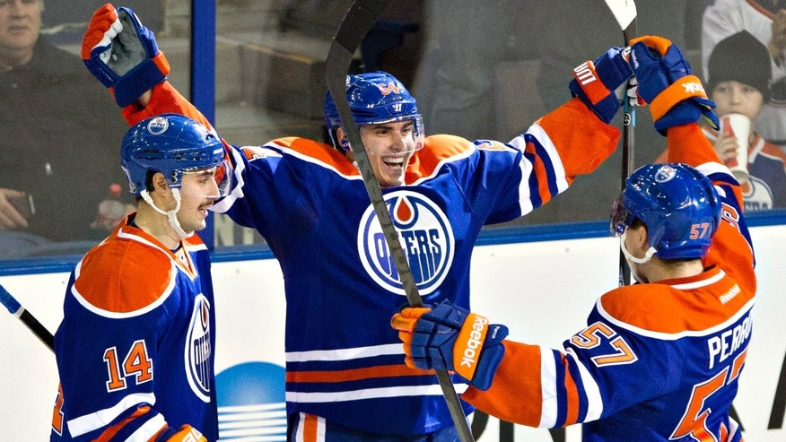 Edmonton Oilers' Jordan Eberle (14) Nail Yakupov (64) and David Perron (57) celebrate a goal on the Columbus Blue Jackets during the second period of an NHL hockey game, Tuesday, Nov. 19, 2013 in Edmonton, Alberta. (AP Photo/The Canadian Press, Jason Franson)