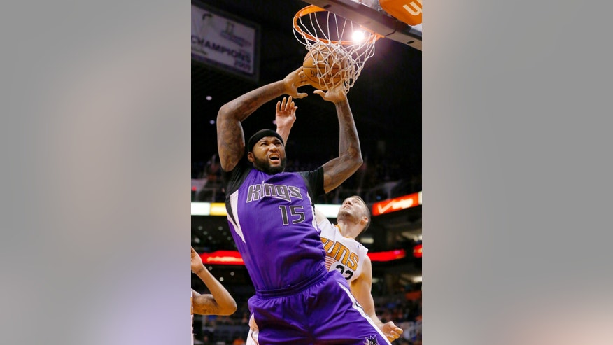 Sacramento Kings' DeMarcus Cousins (15) gets fouled by Phoenix Suns' Miles Plumlee as Cousins tries to dunk the ball during the first half of an NBA basketball game Wednesday, Nov. 20, 2013, in Phoenix. (AP Photo/Ross D. Franklin)