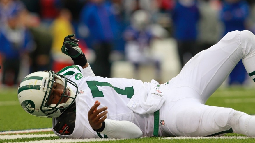 New York Jets quarterback Geno Smith (7) lays on the turf after gettingknocked over by a Buffalo Bill's player during the second half of an NFL football game on Sunday, Nov. 17, 2013, in Orchard Park, N.Y. (AP Photo/Harry Scull Jr,The Buffalo News)