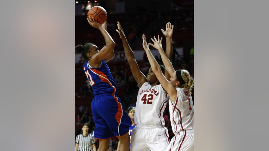 UT Arlington forward Briana Walker, left, goes up for a shot over Oklahoma forward Kaylon Williams, center, and Nicole Kornet, right, during the first half of a NCAA college basketball game in Norman, Okla., Wednesday, Nov. 20, 2013. (AP Photo/Alonzo Adams)
