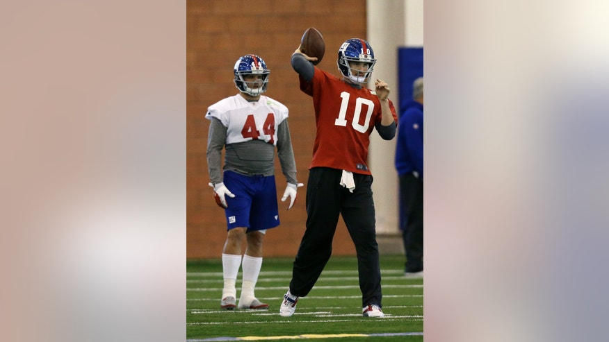 New York Giants running back Peyton Hillis (44) watches as quarterback Eli Manning (10) throws a pass  during NFL football practice in East Rutherford, N.J., Wednesday, Nov. 20, 2013. (AP Photo/Mel Evans)