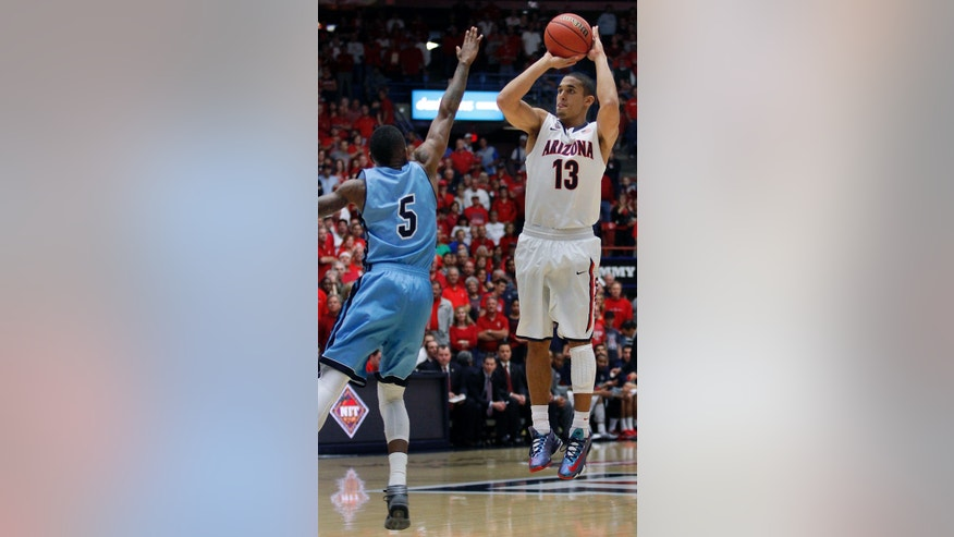 Arizona's Nick Johnson (13) shoots for three over the attempted defense of Rhode Island's Xavier Munford (5) in the first half of an college NCAA basketball game, Tuesday, Nov. 19, 2013 in Tucson, Ariz. This is in the second round of the NIT. (AP Photo/John Miller)