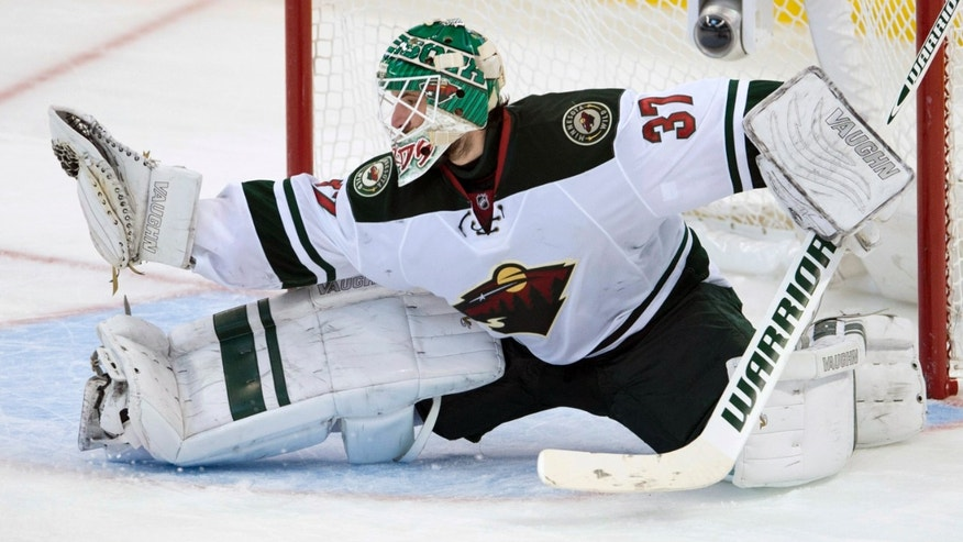 Minnesota Wild goalie Josh Harding makes a save during the second period of an NHL hockey game in Ottawa, Ontario on Wednesday, Nov. 20, 2013. (AP Photo/The Canadian Press, Adrian Wyld)