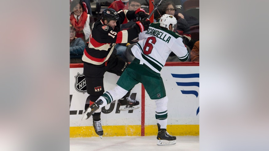 Ottawa Senators center Zack Smith, left, collides with Minnesota Wild defenceman Marco Scandella along the boards during the first period of an NHL hockey game in Ottawa, Ontario on Wednesday, Nov. 20, 2013. (AP Photo/The Canadian Press, Adrian Wyld)