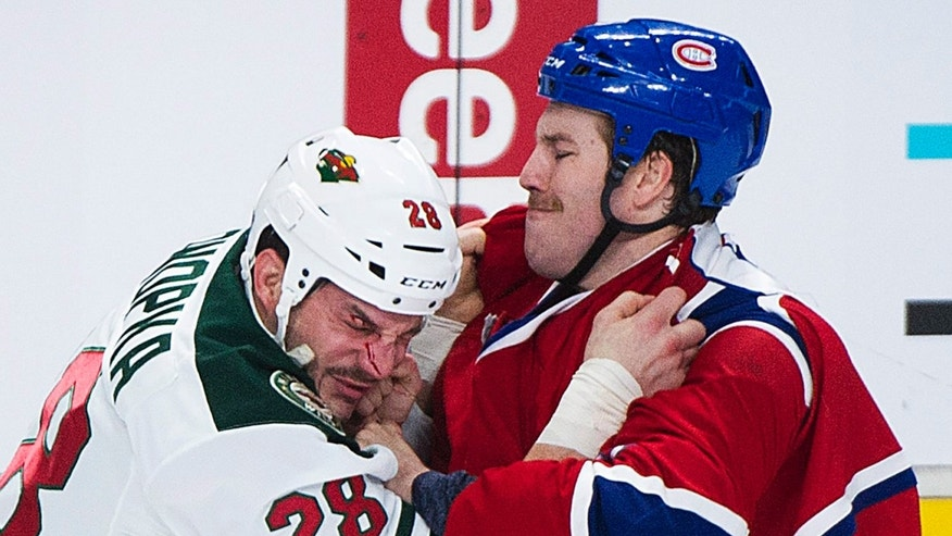 Montreal Canadiens' Brandon Prust, right, fights with Minnesota Wild's Zenon Konopka during the first period of an NHL hockey game, Tuesday, Nov. 19, 2013 in Montreal. (AP Photo/The Canadian Press, Graham Hughes)