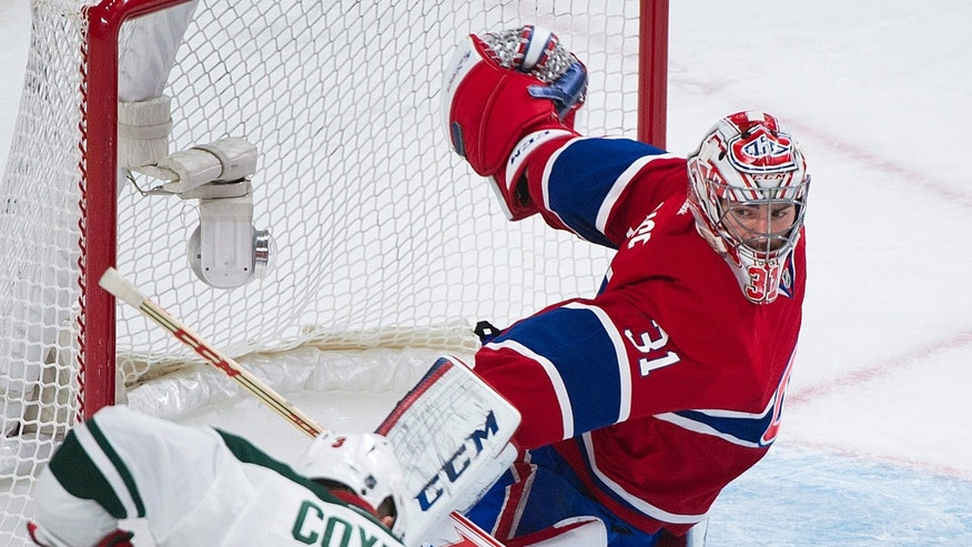 Montreal Canadiens goaltender Carey Price makes a save against Minnesota Wild's Charlie Coyle during the second period of an NHL hockey game, Tuesday, Nov. 19, 2013 in Montreal. (AP Photo/The Canadian Press, Graham Hughes)