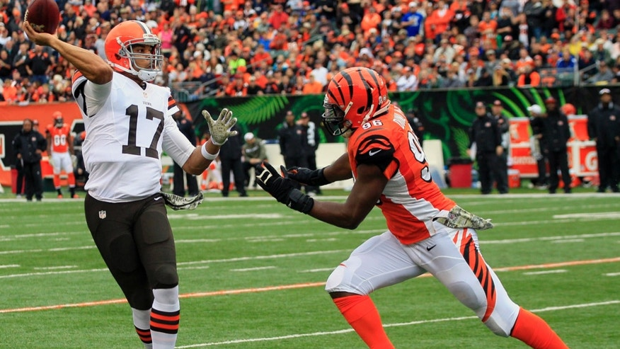 Cleveland Browns quarterback Jason Campbell (17) is pursued by Cincinnati Bengals defensive end Carlos Dunlap (96) in the first half of an NFL football game, Sunday, Nov. 17, 2013, in Cincinnati. (AP Photo/Tom Uhlman)
