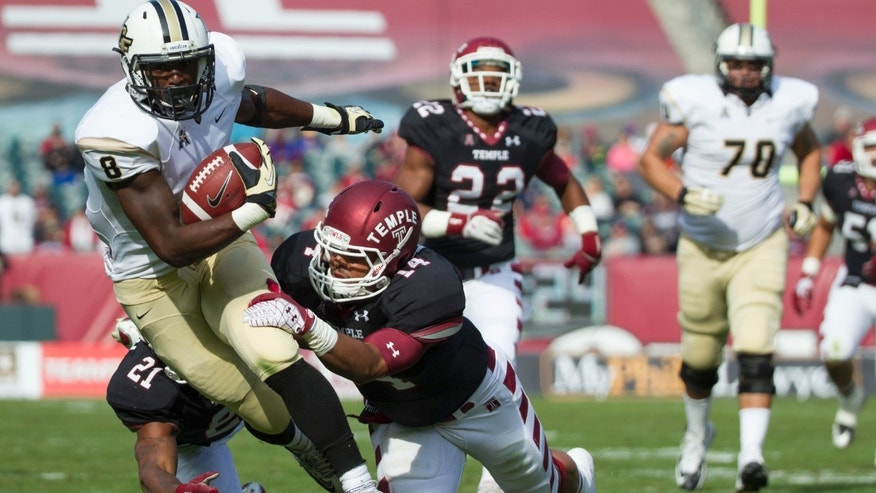 Central Florida running back Storm Johnson (8) runs with the ball as Temple linebacker Jarred Alwan (14) and defensive back Abdul Smith (21) bring him down during the first quarter of  an NCAA college football game, Saturday, Nov. 16, 2013, in Philadelphia.  (AP Photo/Chris Szagola)