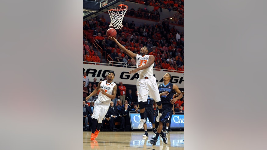 Oklahoma state wing Le'Bryan Nash, left, and Memphis guard Geron Johnson, right, watch as Oklahoma State guard Marcus Smart lofts a shot to the basket during the second half of an NCAA college basketball game in Stillwater, Okla., Tuesday, Nov. 19, 2013.  (AP Photo/Brody Schmidt)