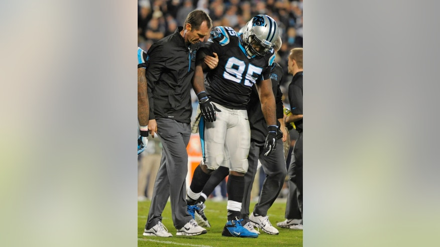 Carolina Panthers' Charles Johnson (95) is helped off the field after being injured against the New England Patriots during the second half of an NFL football game in Charlotte, N.C., Monday, Nov. 18, 2013. (AP Photo/Mike McCarn)