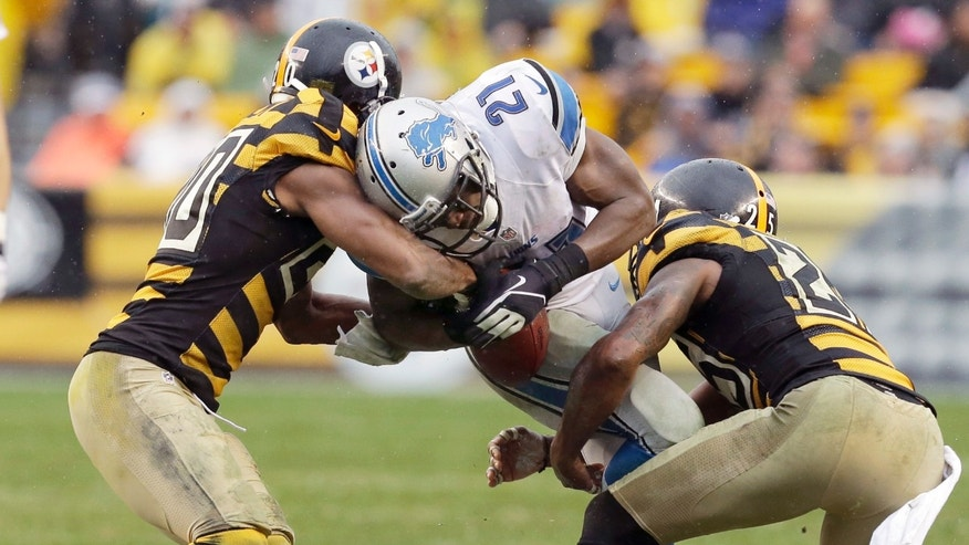 Detroit Lions running back Reggie Bush (21) has the football stripped by Pittsburgh Steelers strong safety Will Allen (20) as free safety Ryan Clark (25) hits him in the first half of an NFL football game in Pittsburgh, Sunday, Nov. 17, 2013. The play was called dead on an early whistle and no fumble was ruled. (AP Photo/Gene J. Puskar)