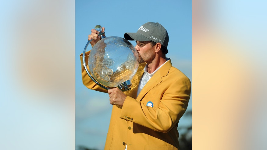 Adam Scott of Australia kisses his trophy after winning the Australian Masters golf tournament at Royal Melbourne Golf Course in Melbourne, Australia, Sunday, Nov. 17, 2013. (AP Photo/Andy Brownbill)
